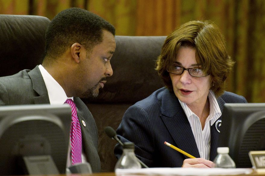 D.C. Council Chairman Kwame R. Brown talks with Ward 3 council member Mary M. Cheh during a legislative session Tuesday. She has proposed a bill that would use about $13 million in general funds to cover delayed out-of-state-bonds taxation. (Drew Angerer/The Washington Times)