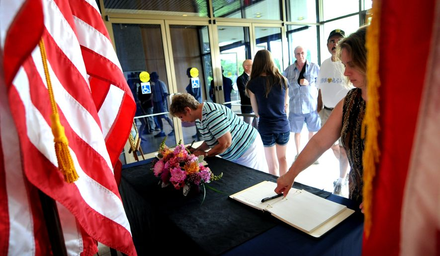 People sign the condolence book for former first lady Betty Ford in the front lobby of the Gerald R. Ford Presidential Museum in Grand Rapids, Mich., on Sunday, July 10, 2011. Mrs. Ford died Friday at age 93. (AP Photo/The Grand Rapids Press, Katy Batdorff)
