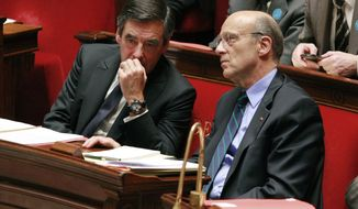 French Prime Minister Francois Fillon (left) speaks with French Foreign Minister Alain Juppe during a debate on the French intervention in Libya at the National Assembly in Paris on Tuesday, July 12, 2011. (AP Photo/Jacques Brinon)