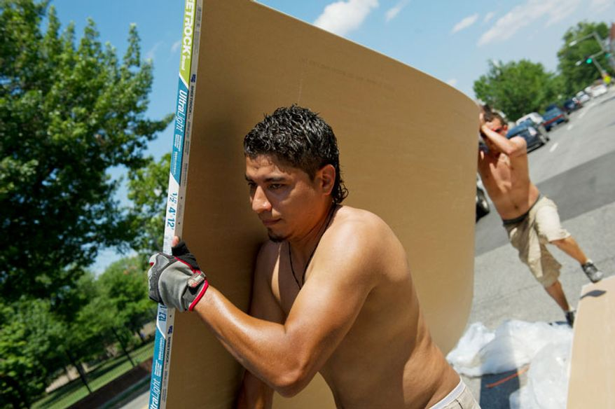 As the temperatures neared 100 degrees today, Edwardo Ramos (left) and Robert Velasquez join other men loading sheet rock into a home at 831 Florida Avenue NE in Washington, D.C., Tuesday, July 12, 2011. (Rod Lamkey Jr/The Washington Times)
