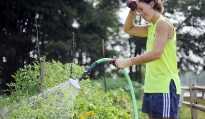 Janet Turner, 42, wipes the sweat off her brow while watering her plot at the Decatur High School Community Garden on Tuesday, July 12, 2011, in Decatur, Ga.  (AP Photo/Erik S. Lesser)
