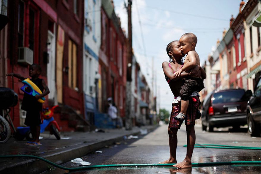 Aniyah Davis, 7, kisses her cousin William Respes, 1, as they play in water from a garden hose to beat the midday summer heat  in Philadelphia, Pa. (AP Photo/Matt Rourke)