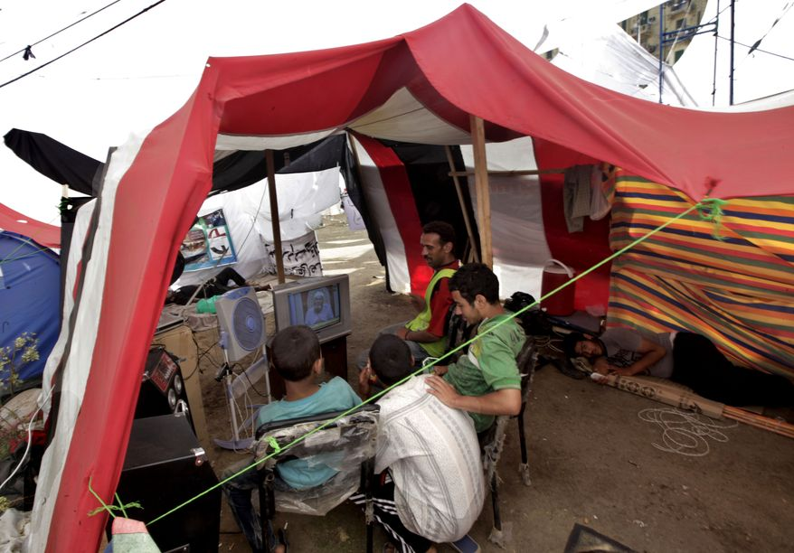 Egyptian demonstrators watch television inside their tent, which sports the colors of the Egyptian flag, during their protest in Tahrir Square in Cairo on Tuesday, July 12, 2011.  (AP Photo/Khalil Hamra)