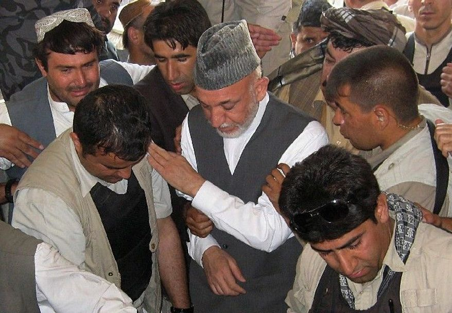 Afghan President Hamid Karzai (center) attends the burial Wednesday of half brother Ahmed Wali Karzai in his family's ancestral village of Karz in Kandahar province. The president's half brother was assassinated at his home Tuesday.