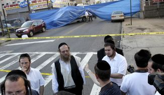 Members of the Orthodox Jewish community and of the media watch police conduct a search of the street where a suitcase believed to contain the remains of 8-year old Leiby Kletzy were found in the Brooklyn borough of New York on Wednesday, July 13, 2011. (AP Photo/Seth Wenig)