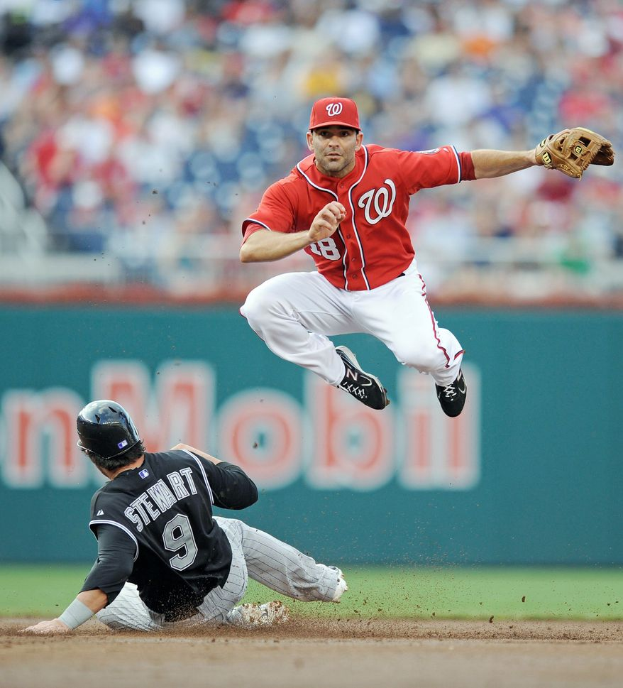 Colorado Rockies' Ian Stewart (9) is out at second as Washington Nationals second baseman Danny Espinosa (18) leaps up in the air after he threw to first to convert a double-play on a grounder by Chris Iannetta during the second inning of a baseball game, Saturday, July 9, 2011, in Washington. (AP Photo/Nick Wass)