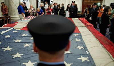 FLAG DAY: Volunteer New York City firefighters stand watch over the National 9/11 Flag on display Thursday at the Russell Senate Office Building. Gallery, www.washingtontimes.com/multimedia/collection. (Barbara L. Salisbury/The Washington Times)
