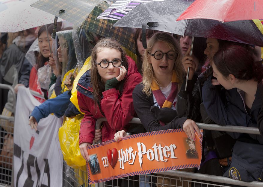 "**FILE** Harry Potter fans wait with umbrellas in the rain outside the cinema in Leicester Square in central London on July 7, 2011, for the world premiere of ""Harry Potter and The Deathly Hallows: Part 2,"" the last film in the series. (Associated Press)"