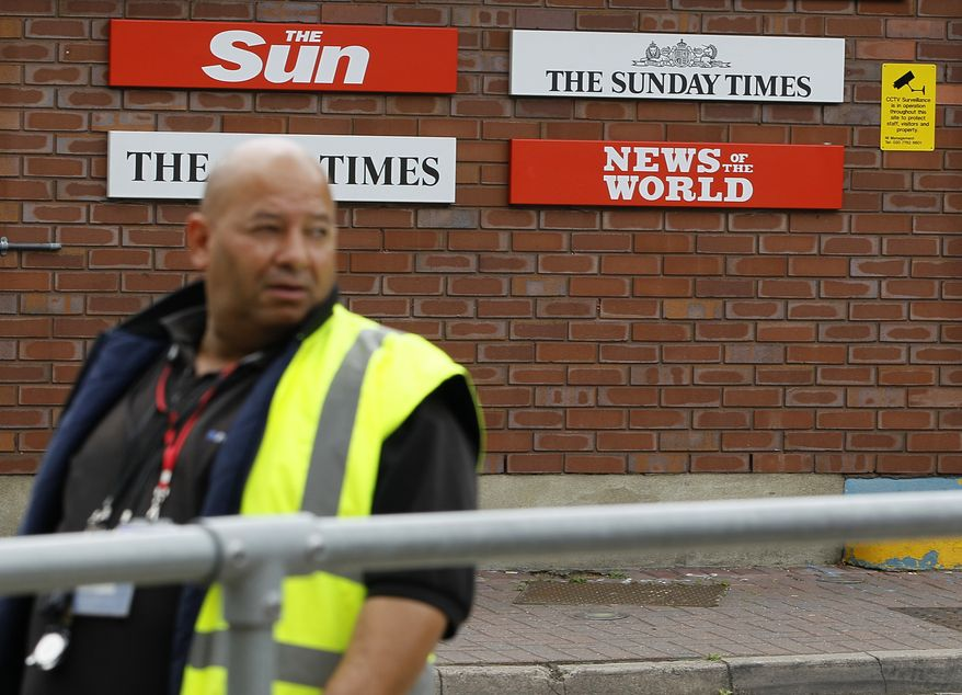 A security guard keeps watch at News International in Wapping, London, on July 14, 2011. (Associated Press)