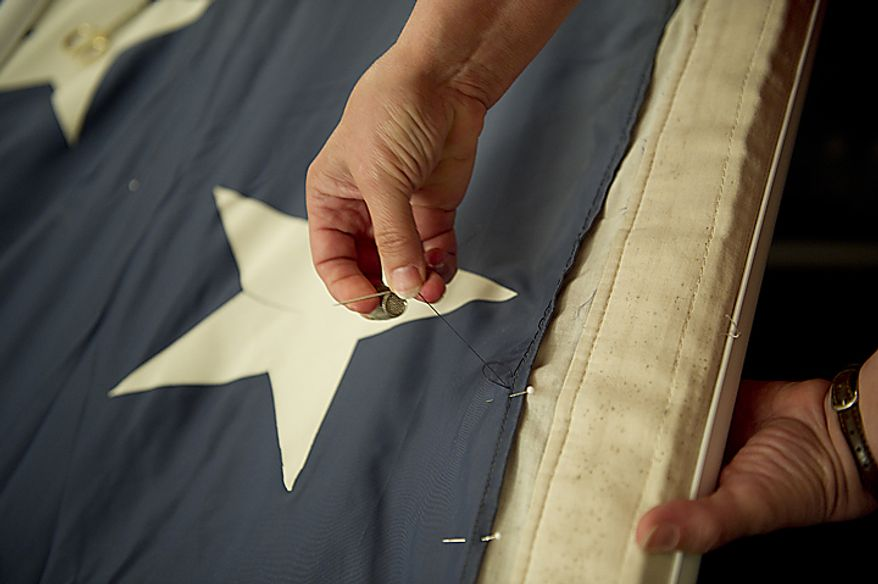 ** FILE ** A woman stitches some of the blue fabric of the official 9/11 American flag during a stitching ceremony in the Russell Senate Office Building in Washington on Thursday, July 14, 2011. This American flag, which was flying just south of the World Trade Center in New York City on Sept. 11, 2001, is making its way around the country and being stitched back together. The goal is to have the flag completed by this Sept. 11, 2011, in time for the 10th anniversary. The finished flag will be on display at the official 9/11 Memorial in New York City. (The Washington Times)