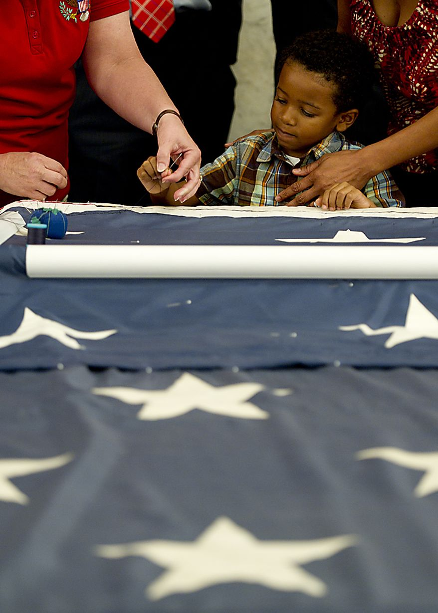 Landon Carter, 4, of Ocoee, Fla., gets help making a stitch in the official 9/11 National flag during a stitching ceremony Thursday, July 14, 2011 at the Russell Senate Office Building in Washington, D.C. Landon's aunt, Maria Ramirez, was killed in the Sept. 11 attack in New York City. This flag was flying just south of the World Trade Center in New York City on Sept. 11, 2001 and is now making its way around the country and is being stitched back together by Americans. The flag is scheduled to be completed by this Sept. 11, in time for the 10th anniversary of the attacks. (Barbara L. Salisbury/The Washington Times)