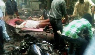 DEVASTATING: A victim of a bomb explosion is carried away moments after detonation at Zaveri Bazaar in Mumbai. Near-simultaneous blasts rocked three upscale neighborhoods during evening rush hour in India's commerce capital Wednesday, killing at least 21 people and injuring 141 others. (Associated Press)