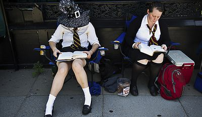 """From left, Maddy Raskulinecz and Claire Wernstedt-Lynch, both of Takoma Park, read the 7th Harry Potter book as they wait for the midnight start of the final Harry Potter movie, near the Uptown Theater along Connecticut Ave. in Cleveland Park, in Washington, D.C., Thursday, July 14, 2011. """"I've probably read the last book five or six times,"""" said Raskulinecz. The friends got in line around 2pm to try to get good seats. (Drew Angerer/The Washington Times)"""