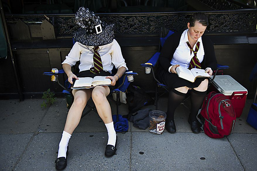 "From left, Maddy Raskulinecz and Claire Wernstedt-Lynch, both of Takoma Park, read the 7th Harry Potter book as they wait for the midnight start of the final Harry Potter movie, near the Uptown Theater along Connecticut Ave. in Cleveland Park, in Washington, D.C., Thursday, July 14, 2011. ""I've probably read the last book five or six times,"" said Raskulinecz. The friends got in line around 2pm to try to get good seats. (Drew Angerer/The Washington Times)"