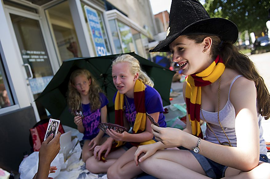 From left, Hannah Parkington, 12, Sadie Parkington, 14, and Sofia Roma, 14, all of the District, play cards to kill time as they wait for the midnight start of the final Harry Potter movie, near the Uptown Theater along Connecticut Ave. in Cleveland Park, in Washington, D.C., Thursday, July 14, 2011. They arrived at 11am and bought tickets for the show over two months ago. (Drew Angerer/The Washington Times)
