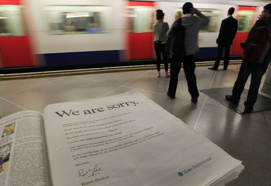"""A newspaper is opened to show the advertisement apology for News International and photographed at a news vendor in central London, Saturday, July 16, 2011. News Corporation chairman Rupert Murdoch signed the company advert titled """"We are sorry,"""" which is published in British national newspapers Saturday. (AP Photo/Sang Tan)"""
