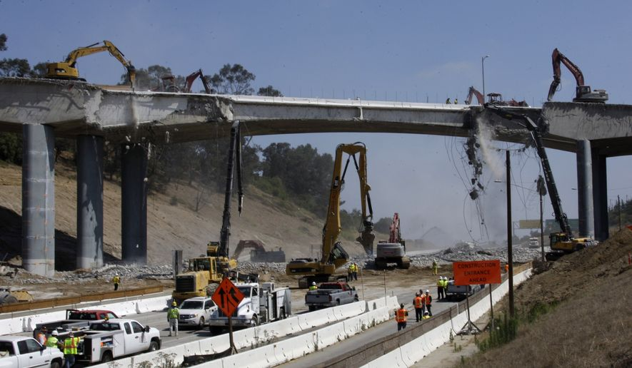 Pneumatic hammers from above and below continue the demolition of two lanes of Mulholland Drive bridge over Interstate 405 in Los Angeles Saturday, July 16, 2011. Ramps to the normally clogged Interstate 405 were shut down Friday evening before the entire roadway was closed at midnight, setting the stage for a 53-hour bridge demolition project that will test whether this car-dependent city can change its driving habits for a weekend. (AP Photo/Reed Saxon)