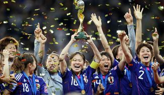 Japanese soccer players celebrate with the trophy after winning their first Women's World Cup on Sunday, July 17, 2011, in Frankfurt, Germany, after defeating the United States in a penalty shootout. (AP Photo/Michael Probst)