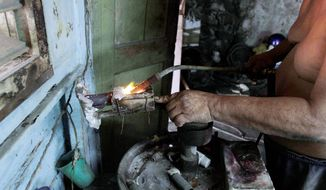A Cuban man who did not want to be identified melts gold to make gold false teeth in his workshop in Havana. (Associated Press)
