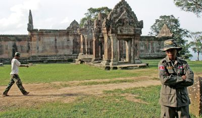 A Cambodian police officer (right) stands near the 11th-century Hindu Preah Vihear temple, near the disputed Cambodia-Thailand border in Preah Vihear province north of Phnom Penh. The U.N.'s highest court on Monday ordered troops from both Thailand and Cambodia to immediately withdraw military forces from disputed areas around the World Heritage temple straddling their border. (Associated Press)