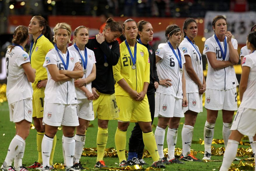 ASSOCIATED PRESS photographs The U.S. team (above) contemplates what might have been after Japan won the Women's World Cup final Sunday in Frankfurt, Germany. Abby Wambach (below) gestures to the crowd after Sunday's loss.