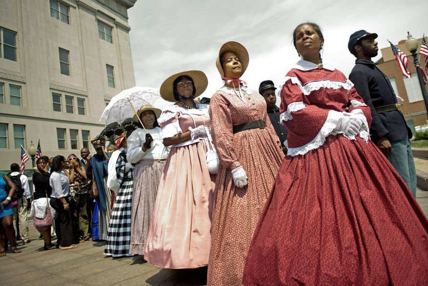 Members of FREED, Female Re-enactors of Distinction, led by Dorothy Stevens (top, far right) and Judy Williams (second from right) get ready to move across Vermont Avenue in Northwest for the reception at the reopening of the African American Civil War Museum on Monday. Soldier re-enactors were part of the program. The District government provided $5 million to help the museum move into the former Grimke School to allow it to expand. Frank Smith, director and founder of the museum, cuts the ribbon to the entrance (above). (Photographs by Drew Angerer/The Washington Times)