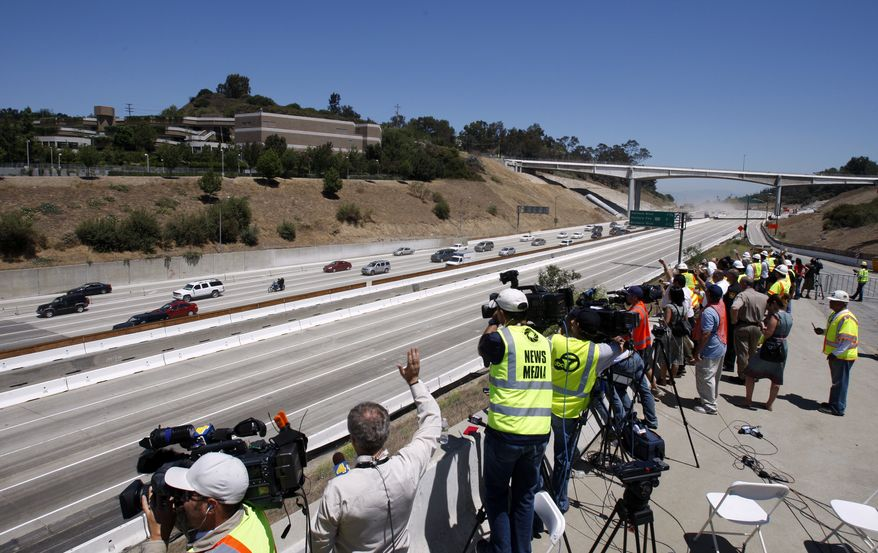 Construction officials and media get a view July 17, 2011, of the first vehicles on southbound Interstate 405 as they approach the Mulholland Drive bridge (in foreground) as demolition of a portion of the bridge is completed before noon in Los Angeles. (Associated Press/Los Angeles Times)