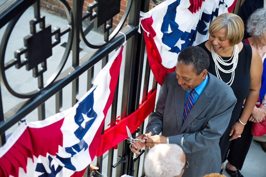 Frank Smith, founder and executive director of the African American Civil War Museum, along with Yvette Alexander (right), cuts the ribbon to the entrance of the museum's new location on Vermont Ave Northwest in Washington on Monday, July 18, 2011. (Drew Angerer/The Washington Times)