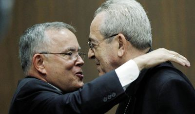Denver Archbishop Charles Chaput (left) and Cardinal Justin Rigali, who is retiring as archbishop of Philadelphia, embrace Tuesday during a news conference in Philadelphia, where the Catholic Church has been rocked by accusations of hiding sex-abuse complaints for decades. (AP Photo)