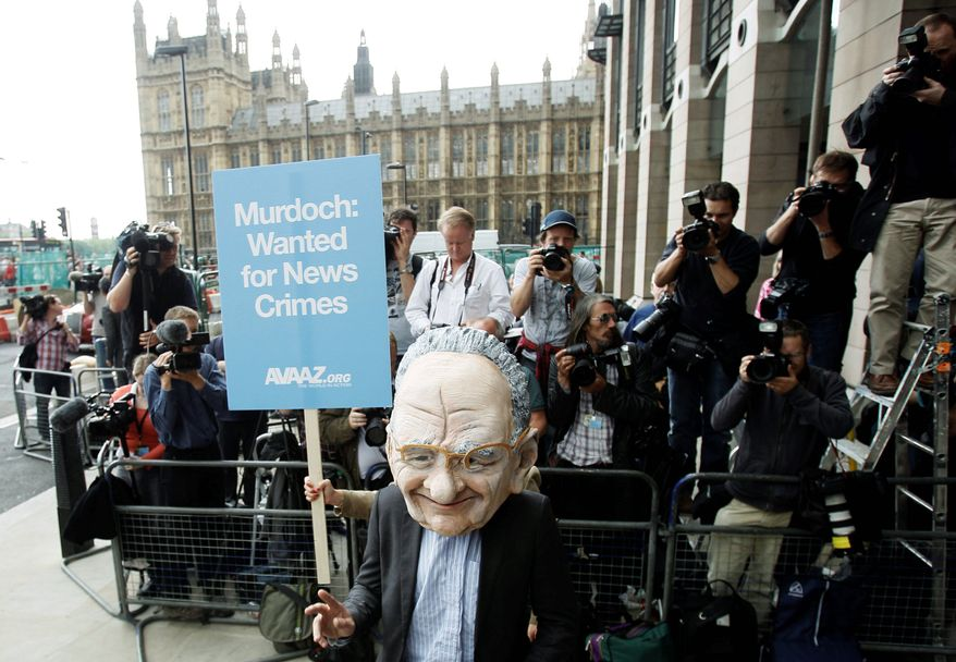 A protester wearing a Rupert Murdoch mask makes his point outside Parliament in London on Tuesday. Mr. Murdoch, CEO of News Corp., and his son James, also a company executive, were questioned for three hours by a parliamentary committee about the ongoing phone-hacking scandal in Britain. (Associated Press)