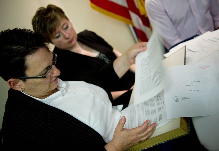 Robin Garber (left), of Staten Island, N.Y., goes through the box of legal documents that she and her wife of five years, Kathleen Cumiskey (right) say they must carry with them everywhere. The box includes their will, medical documents, marriage certificate, civil union certificate and more. (Associated Press)