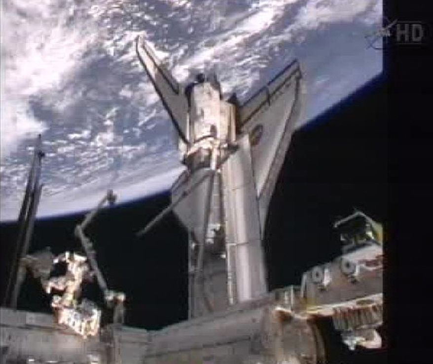 The space shuttle Atlantis, with the Earth behind it, still is docked to the International Space Station early on Tuesday, July 18, 2011, in this image made from NASA TV. (AP Photo/NASA)