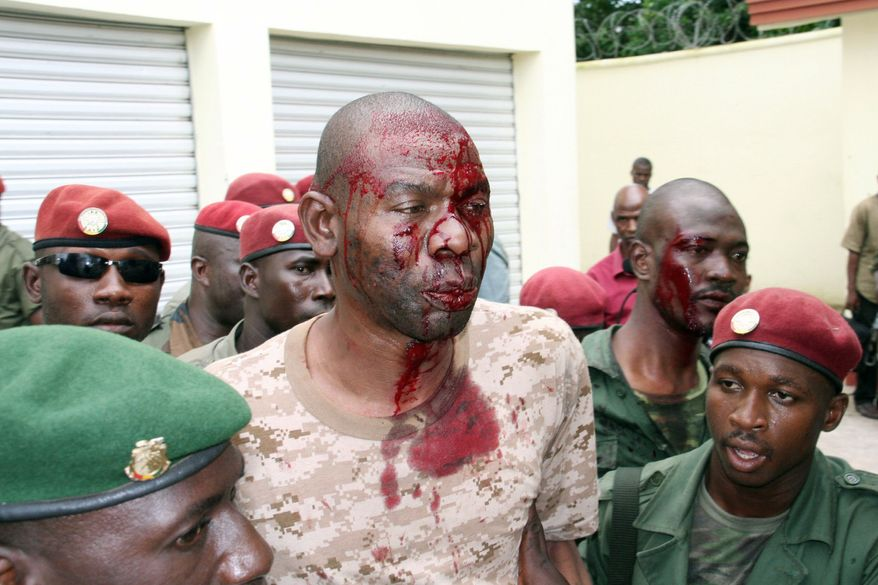 "A bloodied ""De Gaulle,"" a bodyguard close to Guinea's last two military leaders, is detained by presidential guards after shooting broke out near the president's home for a second time Tuesday. (Associated Press)"