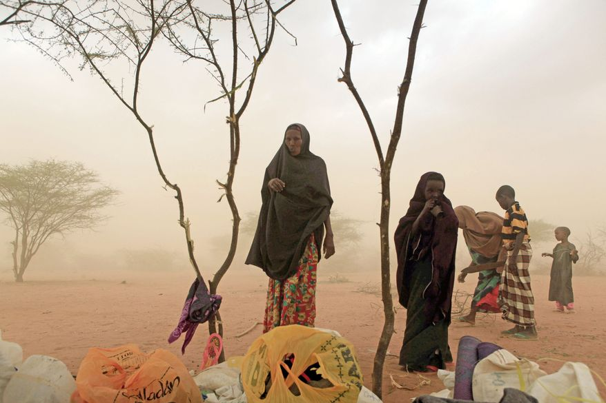 Members of Rage Mohamed's family are overtaken by a dust storm as they try to build a makeshift shelter on the outskirts of the world's largest refugee camp in Dadaab, Kenya, this month. It took the 15-member family five days to walk to the camp from their drought-stricken home in Somalia. (Associated Press)