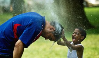 "Gabriel Carvajal of Cali, Colombia, dips his head into a sprinkler while 4-year-old Emmanuel Contreas of Boston rubs his head in Washington on Wednesday. ""The heat is never as bad as this where I live in Colombia,"" Mr. Carvajal said. (Drew Angerer/The Washington Times)"