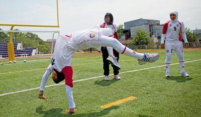 Shahad Ahmed Budebs does a backflip while teammates Houriya Taheri and Alaa Ahmed Hassan (9) watch. (Pratik Shah/The Washington Times)