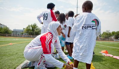 Alaa Ahmed Hassan ties Anthony Gent's shoes during a soccer clinic at Cardozo High School in Washington, D.C. (Pratik Shah/The Washington Times)
