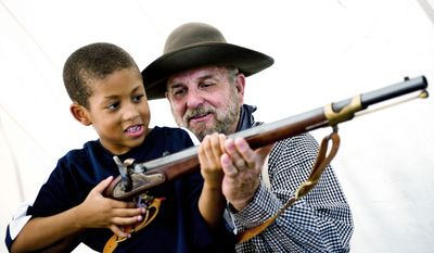 """PHOTOGRAPHS BY DREW ANGERER/THE WASHINGTON TIMES Tommy Phillips of Cookeville, Tenn., shows Malachi Reynolds, 5, of Fairfax how to hold his 1853 Enfield Gun at an encampment near the Manassas Museum on Thursday. """"I just love talking to people about all this history,"""" said Mr. Phillips. Dressed as Gen. Robert E. Lee for the weekend, Al Stone of Hinton, W.Va., stays in the shade under his tent to keep cool. Mr. Stone and his friends were camping out the entire weekend near the Manassas Museum to celebrate the 150th anniversary of the First Battle of Bull Run."""