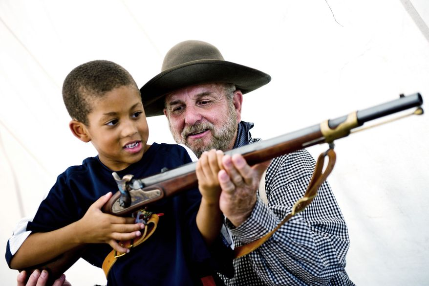 "PHOTOGRAPHS BY DREW ANGERER/THE WASHINGTON TIMES Tommy Phillips of Cookeville, Tenn., shows Malachi Reynolds, 5, of Fairfax how to hold his 1853 Enfield Gun at an encampment near the Manassas Museum on Thursday. ""I just love talking to people about all this history,"" said Mr. Phillips. Dressed as Gen. Robert E. Lee for the weekend, Al Stone of Hinton, W.Va., stays in the shade under his tent to keep cool. Mr. Stone and his friends were camping out the entire weekend near the Manassas Museum to celebrate the 150th anniversary of the First Battle of Bull Run."