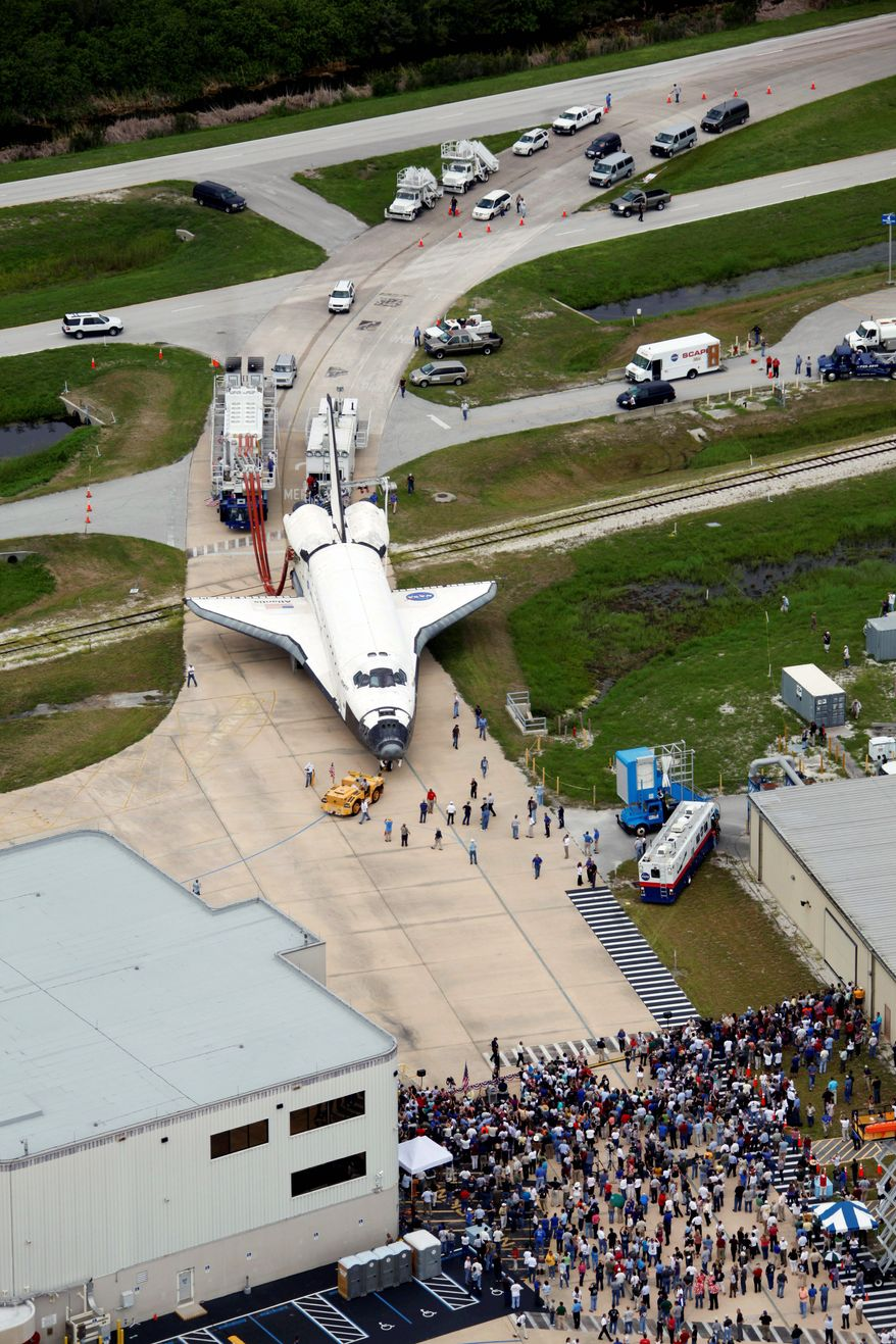 Atlantis is towed to the Orbitor Processing facility as hundreds of NASA employees gather at the Kennedy Space Center at Cape Canaveral, Fla., on Thursday. The landing of Atlantis marks the end of the 30-year program. (Associated Press)