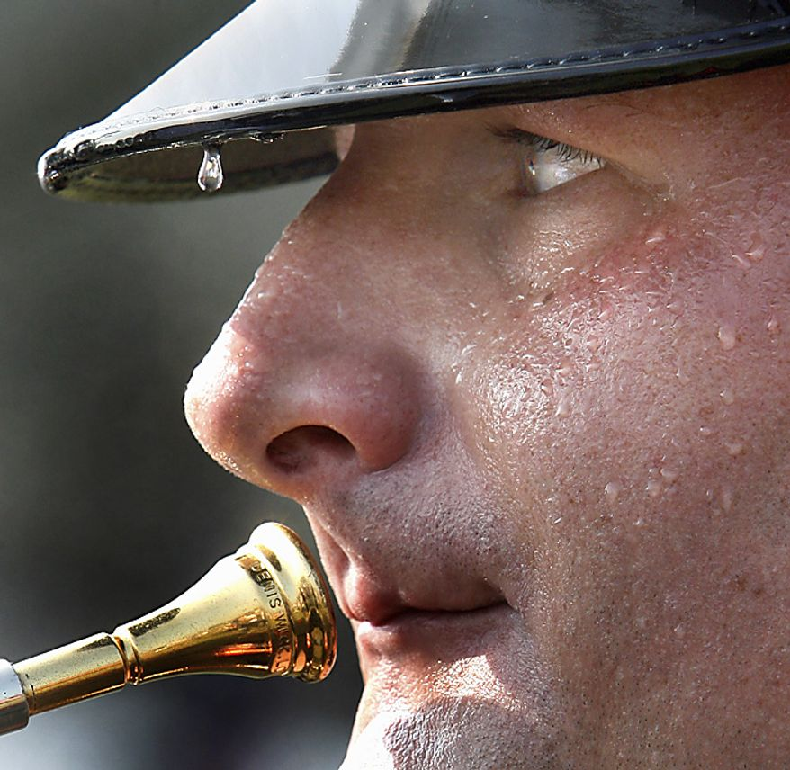 A bead of sweat rolls off the rim of the hat of U.S. Marine Cpl. William Woods of Glen Allen, Va.  as he awaits instuction from the leader of the Quantico Marine Corps Band at Manassas Battlefield Park, Thursday, July 21, 2011.  The band performed in extreme heat during the 150th Anniversary First Battle of Manassas commemorative program. (AP Photo/Richmond Times-Dispatch, P. Kevin Morley)