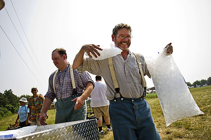 """David Keck, of Allentown, Penn., carries bags of ice back to his encampment at Camp Manassas near Jennie Dean Elementary School, in Manassas, Va., Thursday, July 21, 2011. Keck and his group of friends are celebrating the 150th anniversary of the First Battle of Bull Run/Manassas by dressed as a Confederate Artillery Unit and camping out the entire weekend. """"Even though it's not authentic, I think if they had bags of ice in the Civil War era, they would have used them,"""" said Keck jokingly, who is wearing wool clothing the entire weekend. (Drew Angerer/The Washington Times)"""