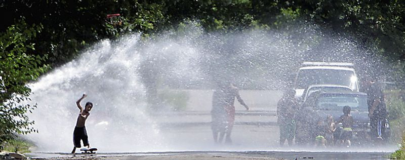A skateboarder rides through an opened fire hydrant in Detroit, Thursday, July 21, 2011 where the National Weather Service says the temperature is expected to reach 100. (AP Photo/Carlos Osorio)