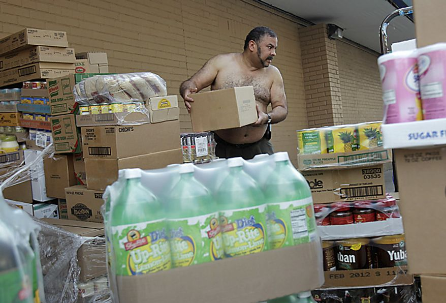 Eddie Ortiz unloads palettes of groceries outside a grocery store in New York, Thursday, July 21, 2011. Because the delivery was four hours late, Ortiz was working through the hottest part of the day. Hot weather that has plagued the Plains for days spread eastward Thursday, blanketing several more states under a sizzling sun and excessive heat warnings that made people sick, shut down summer schools and spurred cities to offer cooling centers and free swimming. (AP Photo/Seth Wenig)