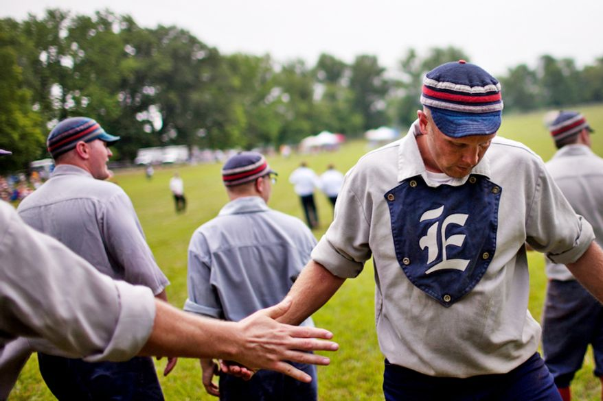 "Elkton Eclipse centerfielder Erik ""Dubs"" Meyers, of Chesapeake, Md., high fives his teammates after scoring a run during the Loudoun Preservation Society's 19th Century Baseball Day at the Oatlands, in Leesburg, Va., Sunday, June 12, 2011. (Drew Angerer/The Washington Times)"