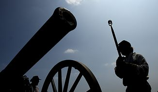 "**FILE** Andy Franklin, of Whitepost, Va., prepares to fire a 10 pound Parrot Rifle cannon, in Manassas, Va., Thursday, July 21, 2011. The Parrot Rifle was capable of hitting targets a mile and a half away and this particular cannon was used in the Civil War movie ""Gods and Generals.""  (Drew Angerer/The Washington Times)"
