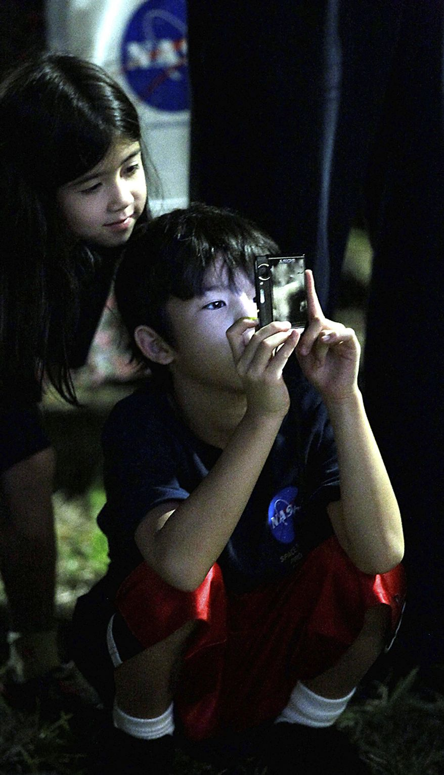 Kenny Fisher (right) takes a photograph as his sister, Ashley (left), looks over his shoulder as they wait at the Johnson Space Center in Houston to watch space shuttle Atlantis land at Kennedy Space Center in Florida on Thursday, July 21, 2011. The landing of the spacecraft brings the shuttle program to an end. (AP Photo/David J. Phillip)