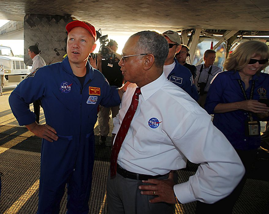 NASA Administrator Charles Bolden (right) and pilot Doug Hurley speak while walking under space shuttle Atlantis after it landed at the Kennedy Space Center at Cape Canaveral, Fla., on Thursday, July 21, 2011. The landing of the spacecraft marks the end of NASA's 30-year shuttle program. (AP Photo/Scott Audette, Pool)