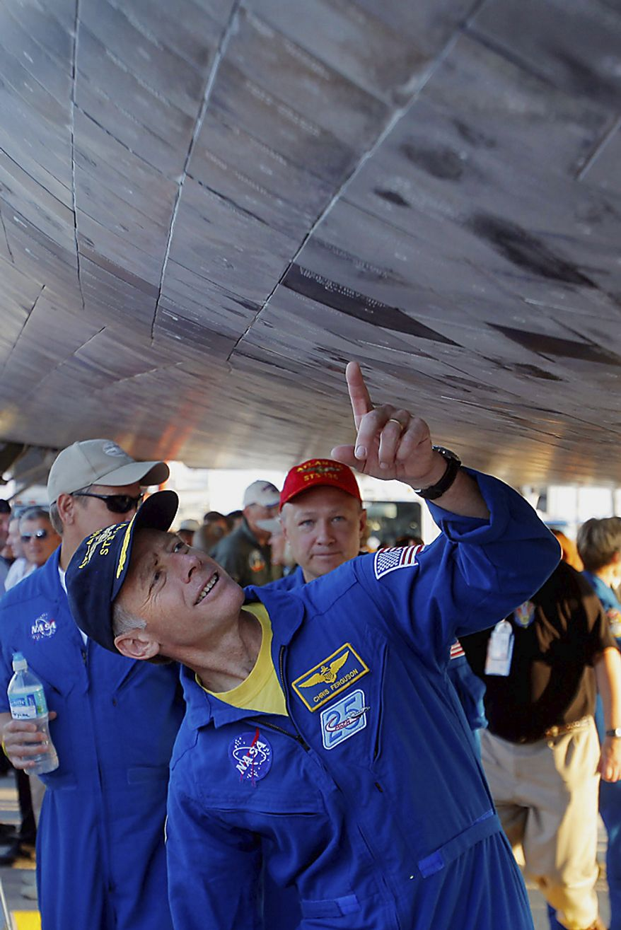 Commander Chris Ferguson points to tiles under space shuttle Atlantis after landing at the Kennedy Space Center at Cape Canaveral, Fla., on Thursday, July 21, 2011. The landing of the spacecraft marks the end of NASA's 30-year shuttle program. (AP Photo/Scott Audette, Pool)
