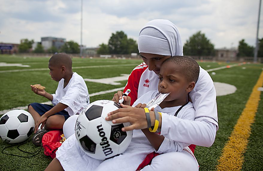 Alaa Ahmed Hassan, 9, of the UAE women's national soccer team, sits with Nathaniel Green, Jr. from the Boys and Girls Club of Greater Washington, as she signs a soccer ball for him during a soccer clinic at Cardozo High School in Northwest Washington, D.C. on Wednesday, July 13, 2011. (Pratik Shah/The Washington Times)